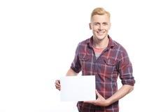 Lächelnder junger Mann, der weißes Blatt Papier hält Stockbild