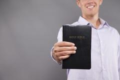 Lächelnder junger Mann hält Bibel an stockbild