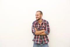 Lächelnder junger Mann im karierten Hemd, das mit den Armen gekreuzt steht Stockfotos