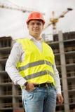 Lächelnder junger Mann im roten Hardhat und grüne Sicherheit bekleiden Stellung auf Baustelle stockfotos