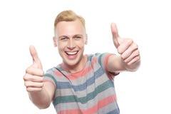 Lächelnder junger Mann mit den Daumen-oben Stockbilder