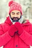 Lächelnder junger Mann mit Schale im Winterwald lizenzfreie stockfotografie