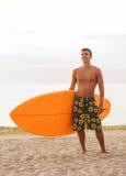 Lächelnder junger Mann mit Surfbrett auf Strand Lizenzfreie Stockbilder