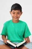 Lächelnder junger Schulejunge 10, der ein Buch liest Stockbilder
