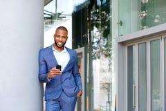 Lächelnder junger schwarzer Geschäftsmann mit einem Mobiltelefon draußen in der Stadt Stockbild