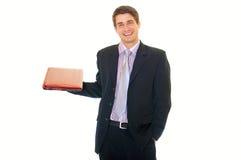 Lächelnder junger stattlicher Geschäftsmannholdinglaptop stockfotos