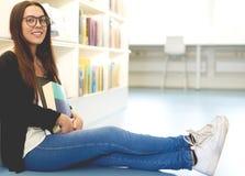 Lächelnder junger Student, der sich auf dem Campus entspannt Stockbild