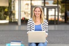 Lächelnder junger Student mit Laptop Stockfotos