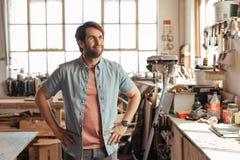 Lächelnder junger Tischler, der oben neue Designe in seiner Werkstatt träumt Stockfotos