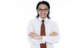 Lächelnder junger Unternehmensleiter mit den Armen gekreuzt Stockbild