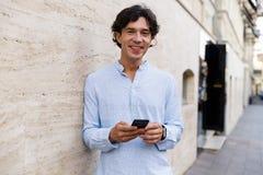 Lächelnder junger zufälliger Mann, der Handy hält lizenzfreie stockfotografie