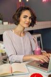 Lächelnder junges Mädchen Blogger, der auf Laptop schreibt Stockfotos