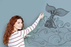 Lächelnder Künstler, der eine Bürste und das Malen eines großen Wals hält Lizenzfreies Stockfoto