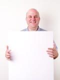Lächelnder kahler Mann, der ein unbelegtes Zeichen anhält stockfotografie
