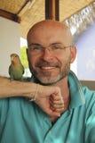 Lächelnder kahler Mann mit einem Bart mit einem Papageien Stockfoto