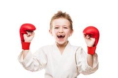 Lächelnder Karatemeisterjunge, der für Sieg gestikuliert  Stockfotos