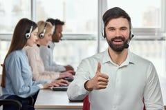 Lächelnder kaukasischer bärtiger Mann mit dem Daumen oben im hellen Büro Stockbilder