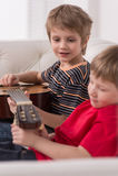 Lächelnder kaukasischer Junge, der Akustikgitarre spielt Lizenzfreies Stockfoto