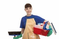 Lächelnder kaukasischer weiblicher Bediensteter With Cleaning Accessories Stockfoto