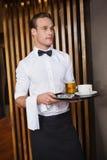 Lächelnder Kellner, der Behälter mit Kaffeetasse und halbem Liter Bier hält Lizenzfreies Stockfoto