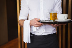 Lächelnder Kellner, der Behälter mit Kaffeetasse und halbem Liter Bier hält Stockfotos