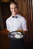 Lächelnder Kellner, der Behälter mit Kaffeetasse und halbem Liter Bier hält Stockbilder