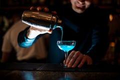 Lächelnder Kellner, der neues Getränk mit blauem Alkohol von einem Schüttel-Apparat in ein Glas unter Verwendung des Siebs gießt Lizenzfreies Stockfoto