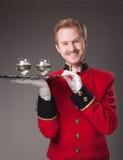 Lächelnder Kellner in der roten Uniform Stockfotografie