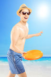 Lächelnder Kerl in den Schwimmenkurzen hosen, die frizbee, auf einem Strand werfen Stockfoto