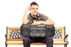 Lächelnder Kerl, der ein boombox gesetzt auf einer Holzbank hält Stockfotografie