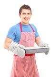 Lächelnder Kerl, der Handschuhe und Schutzblech kochend trägt Lizenzfreies Stockfoto