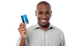 Lächelnder Kerl, der Kreditkarte hält lizenzfreies stockfoto