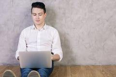 Lächelnder Kerl, der Laptop verwendet lizenzfreie stockfotos