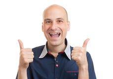 Lächelnder Kerl, der sich Daumen zeigt Stockfoto