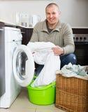 Lächelnder Kerl, der Waschmaschine verwendet Stockfotos