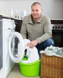Lächelnder Kerl, der Waschmaschine verwendet Stockfotografie