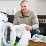 Lächelnder Kerl, der Waschmaschine verwendet Lizenzfreies Stockbild