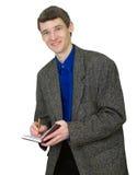 Lächelnder Kerl in einer Klage mit einem Notizbuch in den Händen Stockfoto