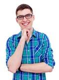 Lächelnder Kerl mit der Hand auf Kinn Stockfoto