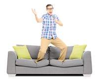 Lächelnder Kerl mit Mikrofon singend und auf einem modernen sof stehend Stockfotografie