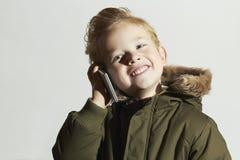 Lächelnder kleiner Junge, der auf dem Mobiltelefon spricht glückliches Kind im Wintermantel Kinder in der erwachsenen Kleidung Ki Stockbilder