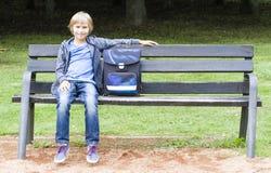Lächelnder kleiner Junge, der auf einer Holzbank mit seinem Rucksack sitzt Bildung, Schule, Lebensstil, Leutekonzept Stockbild