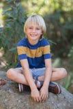 Lächelnder kleiner Junge, der auf Felsen im Wald sitzt Stockfotos