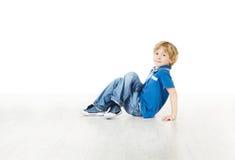 Lächelnder kleiner Junge, der auf weißem Boden sitzt Lizenzfreie Stockfotografie
