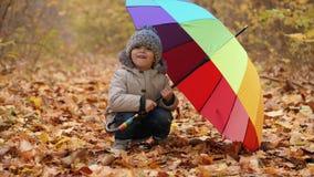 Lächelnder kleiner Junge, der aus einem Regenbogenregenschirm heraus späht stock video
