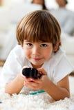 Lächelnder kleiner Junge, der eine entfernte Station anhält Stockfotografie