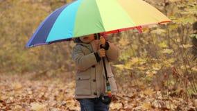 Lächelnder kleiner Junge, der einen mehrfarbigen großen Regenschirm hält stock video