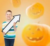 Lächelnder kleiner Junge, der großen weißen Pfeil hält Stockfoto