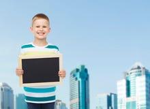 Lächelnder kleiner Junge, der leere schwarze Tafel hält Lizenzfreie Stockbilder