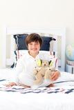 Lächelnder kleiner Junge, der mit einem Teddybären spielt Lizenzfreies Stockbild